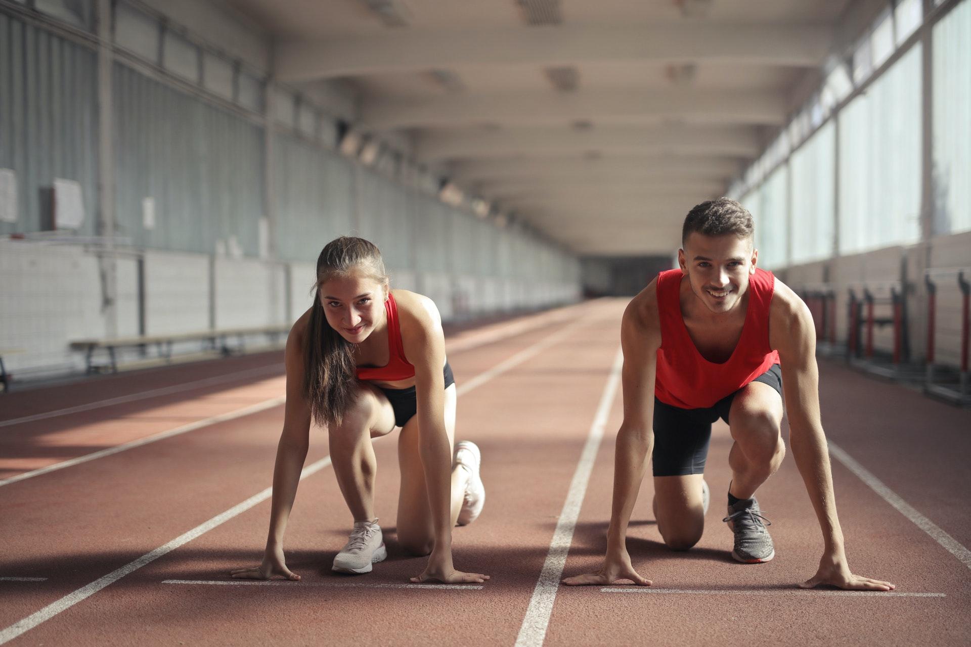 Man en vrouw in sportoutfit maken zich klaar om te gaan lopen in sporthal